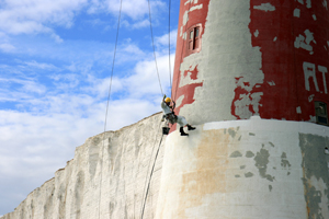 Abseiling painter at the Beachy Head Lighthouse painting the stripes